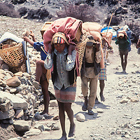 Porters carry loads for trekkers hiking  around Annapurna in Nepal.