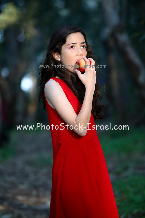 Young girl in red dress eats an apple outdoors