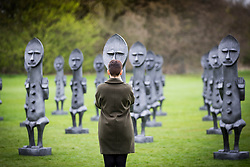 © Licensed to London News Pictures. 07/04/2017. Wakefield UK. A woman takes photographs of Artist Zak Ove's 80 identical 2 metre tall graphite figures called Black & Blue: The invisible Man & the Masque of Blackness that are now on show at Yorkshire Sculpture Park. Photo credit: Andrew McCaren/LNP