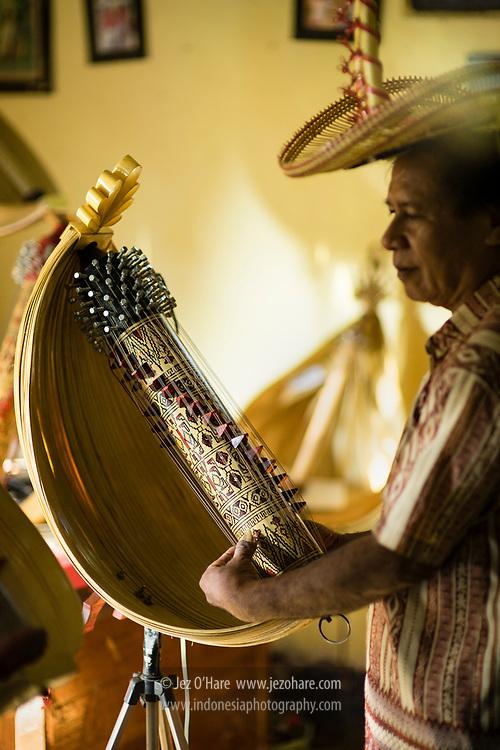 Pengrajin dan pemain alat musik Sasando, Herman A. Ledo. Bapak Herman mengunakan topi Ti'i Langga. Busalangga, Pulau Rote, Nusa Tenggara Timur, Indonesia.