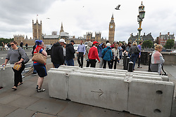 People make their way past barriers on Westminster Bridge in London which have been placed there overnight following Saturday's terrorist attack.