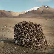 """Stacking dry dung, used as fuel. Life in Baiqara, a Wakhi High pasture inhabited for about 6 months of the year, from May until October. Guiding and photographing Paul Salopek while trekking with 2 donkeys across the """"Roof of the World"""", through the Afghan Pamir and Hindukush mountains, into Pakistan and the Karakoram mountains of the Greater Western Himalaya."""