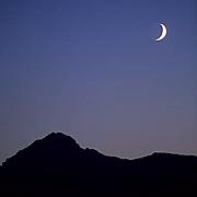 Mountains, a cresent moon rises over the Bridger mountains. Montana.