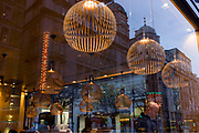 A bald-headed man sitting in the window, under lighting of a central London cafe. The customer sits looking down surrounded by the hanging spherical lights that merge with the background of city architecture beyond.