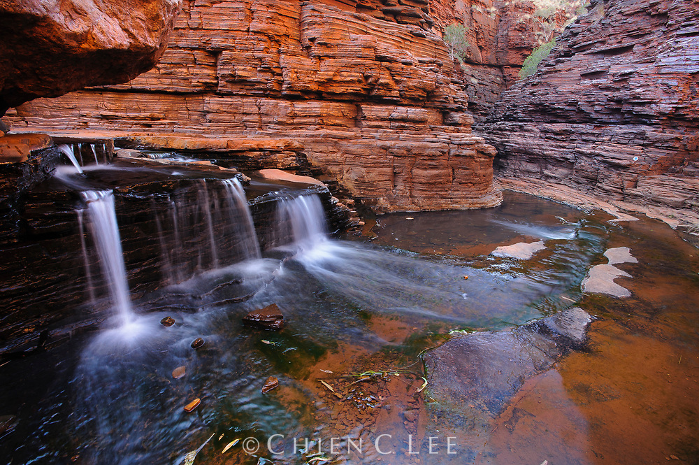 A waterfall cascades through a red rock canyon in Karijini National Park, Western Australia.