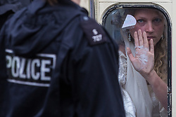 An Extinction Rebellion activist dressed as a bride crouches, glued to a window, in the stairwell of a vintage bus used to block a road junction to the south of London Bridge on the ninth day of their Impossible Rebellion protests on 31st August 2021 in London, United Kingdom. Extinction Rebellion are calling on the UK government to cease all new fossil fuel investment with immediate effect.
