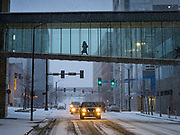 10 JANUARY 2020 - DES MOINES, IOWA: A person uses the skywalk to get across Mulberry Street during a snowstorm in downtown Des Moines Friday. The first significant snow in two months blanketed Des Moines Friday evening. Meteorologists are predicting up to six inches of snow overnight and have issued a winter storm warning for southern and central Iowa. Most schools in the affected area closed early and cancelled afternoon events. Some presidential candidates, campaigning ahead of the Iowa Caucuses, cancelled their events.    PHOTO BY JACK KURTZ