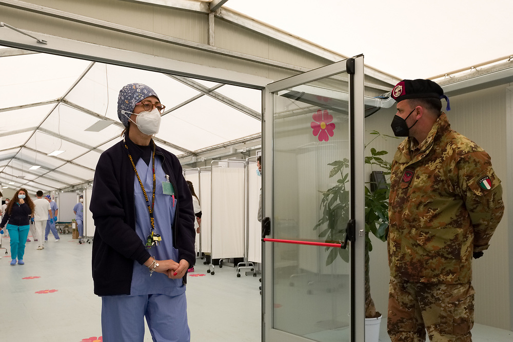 """A nurse and a soldier stand in the Covid Vaccine Center on March 4, 2021 set up in the """"Ferrari-Orsi"""" barracks of the Brigata Bersaglieri Garibaldi (Bersaglieri Garibaldi Brigade) in Caserta, southern Italy, as part of vaccinations for teachers and school staff. The center is the largest in the Campania region, with 26 stations where up to three thousand vaccines can be administered per day."""