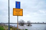 Nederland, Nijmegen, 9-2-2020 Het waterpeil in de rivier de Waal. De Nevengeul bij Lent stroomt vol en ontlast de hoofdstroom van de rivier. Door een verhoogde waterstand stroomt het rivierwater over de drempel de Spiegelwaal in. Een bord waarschuwt voor het doodlopen van de weg wegens hoogwater .  Foto: Flip Franssen