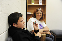 In the front lobby of the Chinatown Health Services Center in Salinas, Nathaniel Ashlin, 11, folds a dollar bill into various shapes as his mother Joan Sassman looks on.