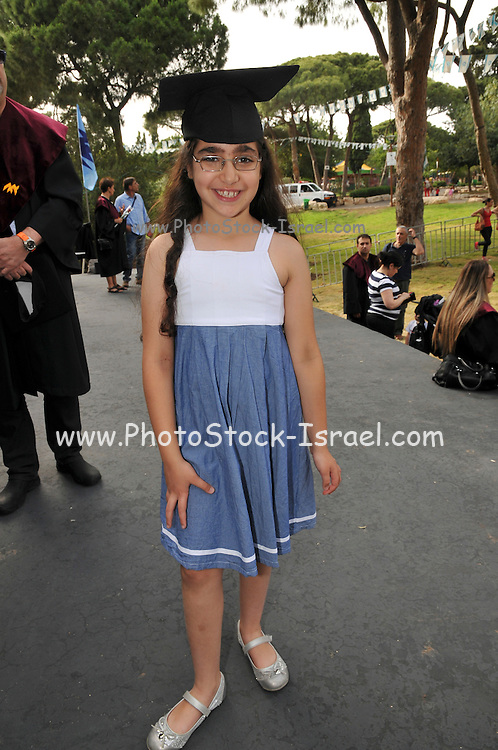 Young girl of 8 wears a Mortarboard at a doctoral ceremony at a university