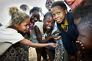 Children with fresh water, the result of using a PlayPump near Pretoria, South Africa. The PlayPump Water System uses the energy of children at play to operate a water pump. It is manufactured by the South African company Roundabout Outdoor. It operates in a similar way to a windmill-driven water pump. The PlayPump water system is a like a playground merry-go-round attached to a water pump. The spinning motion pumps underground water into a 2,500-liter tank raised seven meters above ground. The water in the tank is easily dispensed by a tap valve. According to the manufacturer the pump can raise up to 1400 liters of water per hour from a depth of 40 meters. Excess water is diverted below ground again. The storage tank has a four-sided advertising panel. Two sides are used to advertise products, thereby providing money for maintenance of the pump, and the other two sides are devoted to public health messages. There are more than 1000 PlayPump systems in five countries of Sub-Saharan Africa, providing clean drinking water to more than 1 million people in need.