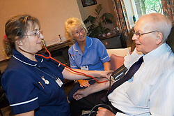 Discharged elderly patient is visited in his home by district nurse & health support worker to check his blood pressure Bradford Yorkshire UK