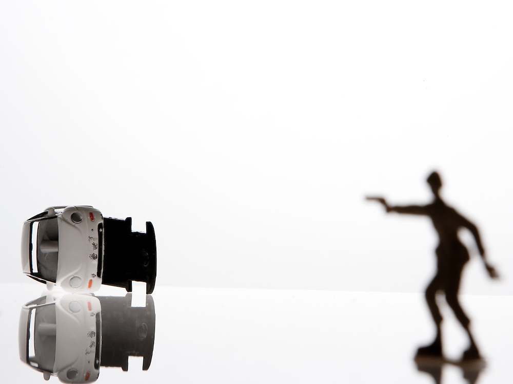Conceptual image of a toy solder shooting at a turned over toy  Car