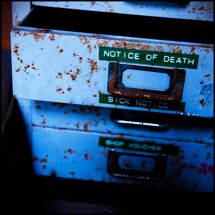 """Rusting metal drawers labelled """"notice of death"""" and """"sick notice""""."""