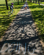 People ride over a chalk sign that says 'You're doing great considering' - Clapham Common is reasonably busy as the sun is out and it is warmer. The 'lockdown' continues for the Coronavirus (Covid 19) outbreak in London.