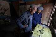 A Chinese Calligrapher making signs using traditional calligraphy in his shop in Shaxi, Yunnan Province, China.