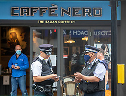 © Licensed to London News Pictures. 14/08/2020. London, UK. Police attend Cafe Nero next to Victoria Coach Stn in Westminster after reports of an incident where a member of the public became aggressive while not wearing a face mask. A large police presence at Victoria Station this morning as Prime Minister Boris Johnson announces that fines for not wearing a face mask on public transport and shops will rise to £3,200. Photo credit: Alex Lentati/LNP