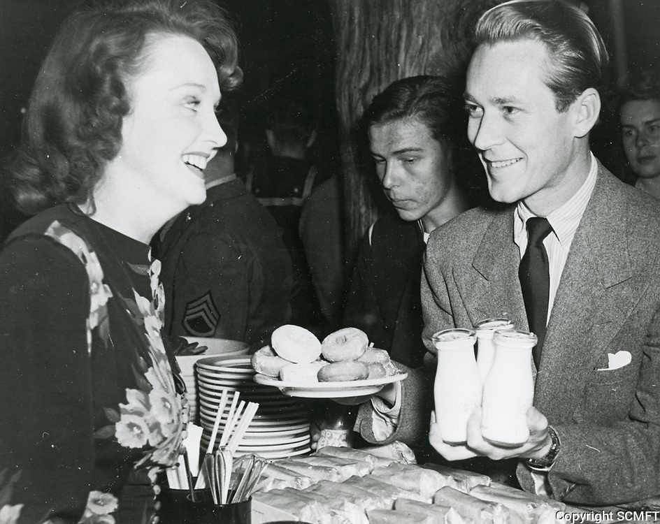 1944 Actor, Jess Barker holds a tray of milk and donuts while chatting with a volunteer hostess at the Hollywood Canteen