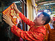 27 JANUARY 2017 - BANGKOK, THAILAND:      A man puts up Chinese New Year decorations at Wat Mangkon Kamalawat on Chinese New Year in Bangkok. 2017 is the Year of the Rooster in the Chinese zodiac. This year's Lunar New Year festivities in Bangkok were toned down because many people are still mourning the death Bhumibol Adulyadej, the Late King of Thailand, who died on Oct 13, 2016. Chinese New Year is widely celebrated in Thailand, because ethnic Chinese are about 15% of the Thai population. Wat Mangkon Kamalawat is a Thai-Chinese Buddhist temple.   PHOTO BY JACK KURTZ