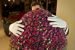 © Licensed to London News Pictures. 22/01/2011 London, UK. A concierge adjusts a giant egg designed by fashion designer Mary Katrantzou in the lobby of The May Fair Hotel, London. The egg is one of 200 hidden around the capital. Egg hunters who find them are in with the chance of winning a Faberge egg worth £100,000..Photo credit : Simon Jacobs/LNP