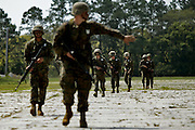 The point man gives his platoon some instruction on a simulated patrol during Crucible.  The Crucible is a A 52 hour final test in their recruit training and represents the culmination of all of the skills and knowledge a marine should possess.  Marine Corps Recruit Depot at Parris Island in South Carolina is where all male recruits living east of the Mississippi River and all female recruits from all over the US receive their arduous twelve week training in their quest to become marines. Even though there are two current active wars and a weak economy, recruitment has not been effected.  Actually, recruiting numbers have increased, with more young men and women looking toward the military for answers.