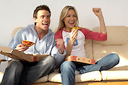 couple sitting on sofa eating pizza and chips while watching the television supporting a sporting event, punching the air, cheering<br />