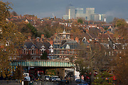 With Canary Wharf rising tall in the distance, traffic eases under the railway bridge and through the junction of Herne Hill in south London on 18th November 2016, in Herne Hill, Lambeth SE24 south London, England.