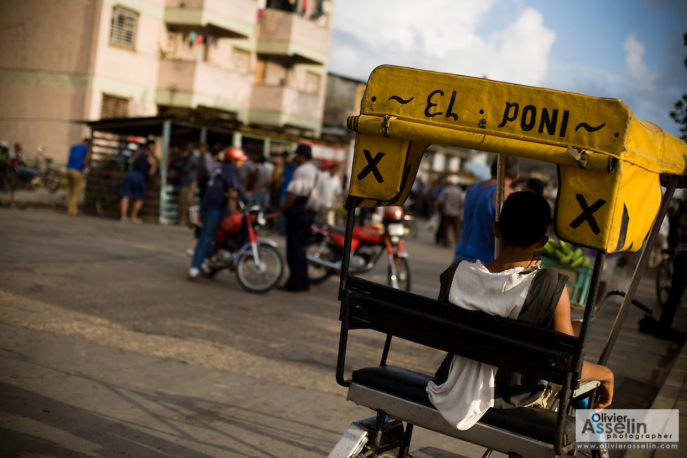 """The driver of a bicycle taxi named """"The Pony"""" rests in his vehicle in Baracoa, Cuba on Sunday July 13, 2008."""