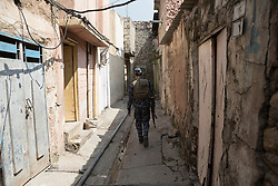 Licensed to London News Pictures. 02/04/2017. Mosul, Iraq. An Iraqi Federal Police officer walks through an alleyway in West Mosul's Old City. The close nature of the city's older districts, where some alleys are only wide enough for one person to walk, mean that Iraqi forces are having to advance cautiously to avoid civilian and military casualties.<br /> <br /> Iraqi forces continue to fight house to house as they push further into West Mosul. Iraqi forces are now advancing on the city's old districts where Islamic State fighters still hold out. Photo credit: Matt Cetti-Roberts/LNP