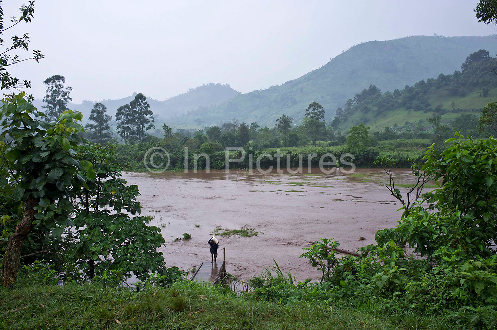 A man walks across the school football pitch after floods in the village of Buhoma, Uganda.
