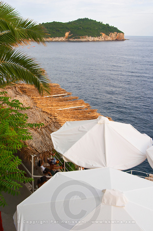 White sun shade umbrellas at a cafe on the city wall overlooking the sea and the Lokrum island Dubrovnik, old city. Dalmatian Coast, Croatia, Europe.