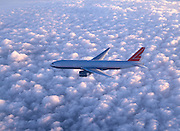 Boeing 777 flying above puffy clouds
