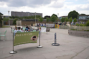 Park Life Cafe and playground in Burgess Park on 31st July 2015 in South London, United Kingdom. On the horizon is the Aylesbury Estate, a large housing estate located in Walworth, South East London. It contains 2,704 dwellings and was built between 1963 and 1977. The whole estate is currently undergoing a major redevelopment with most of the dwellings are derelict.