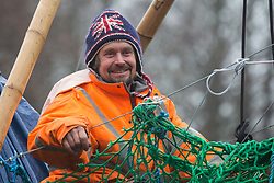 Denham, UK. 8th December, 2020. Dan Hooper, widely known as Swampy during the 1990s, sits on a bamboo tripod positioned in the river Colne. The climate and roads activist had occupied the tripod the previous day in order to delay the building of a bridge as part of works for the controversial HS2 high-speed rail link and a large security operation involving officers from at least three police forces, the National Eviction Team and HS2 security guards was put in place to facilitate his removal.