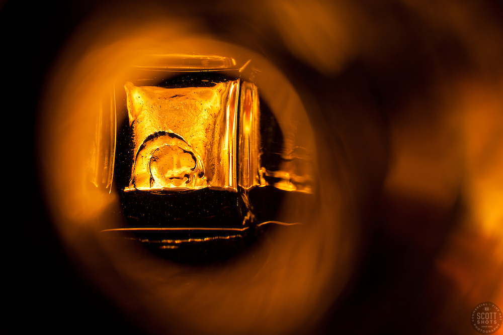 """""""Beauty at the Bottom: Tequila 10"""" - This is a photograph of a tequila bottle, shot right down inside the mouth of the bottle. A fire behind the bottle provides the light source and the color of the image."""