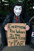 Demonstration against any intervention in Syria called by Stop the War and CND, August 30th 2013, Central London. A man wearing a V for Vendetta mask ,as worn by Occupy activists,holds a placard which has the Jack Canfield quote 'Everything you want is the other side of fear'.