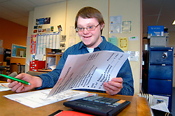 Young man with learning disabilities reading large print bank statement; community centre; Bradford; Yorkshire UK