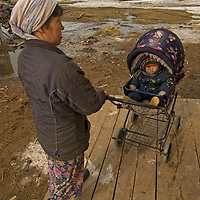 North of the Arctic Circle in Russia, a Nenet woman and her baby wait outside a store in Snopa village.  The Nenet are a mongoloid ethnicity  and are the primary reindeer herders of northern Russia (though, unlike the local Komi people, none herd reindeer nomadically in this region).