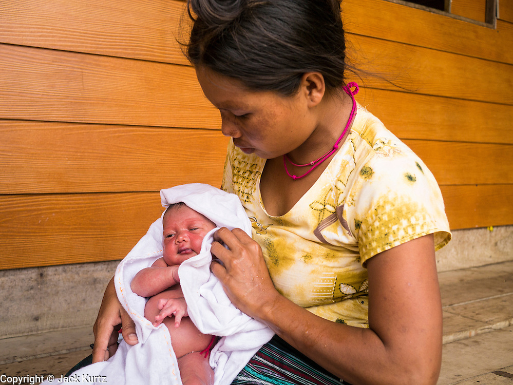 21 MAY 2013 - MAE KU, TAK, THAILAND:  A Burmese woman with her newborn at the SMRU clinic in Mae Ku. Health professionals are seeing increasing evidence of malaria resistant to artemisinin coming out of the jungles of Southeast Asia. Artemisinin has been the first choice for battling malaria in Southeast Asia for 20 years. In recent years though,  health care workers in Cambodia and Myanmar (Burma) are seeing signs that the malaria parasite is becoming resistant to artemisinin. Scientists who study malaria are concerned that history could repeat itself because chloroquine, an effective malaria treatment until the 1990s, first lost its effectiveness in Cambodia and Burma before spreading to Africa, which led to a spike in deaths there. Doctors at the Shaklo Malaria Research Unit (SMRU), which studies malaria along the Thai Burma border, are worried that artemisinin resistance is growing at a rapid pace. Dr. Aung Pyae Phyo, a Burmese physician at a SMRU clinic just a few meters from the Burmese border, said that in 2009, 90 percent of patients were cured with artemisinin, but in 2010, it dropped to about 70 percent and is now between 55 and 60 percent. He said the concern is that as it becomes more difficult to clear the parasite from a patient, progress that has been made in combating malaria will be lost and the disease could make a comeback in Southeast Asia.  PHOTO BY JACK KURTZ