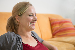 Mature woman sitting on couch, smiling
