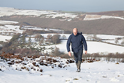 © Licensed to London News Pictures. 14/01/2015. Wheddon Cross, Devon, UK. A man walking on Dunkery Hill in Exmoor National Park, Devon this morning, 14th January 2015. Snow has fallen overnight across many parts of England, causing travel disruption in some areas.  Photo credit : Rob Arnold/LNP