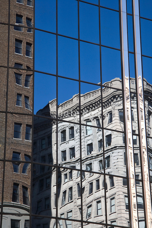 old buildings reflecting in a modern building