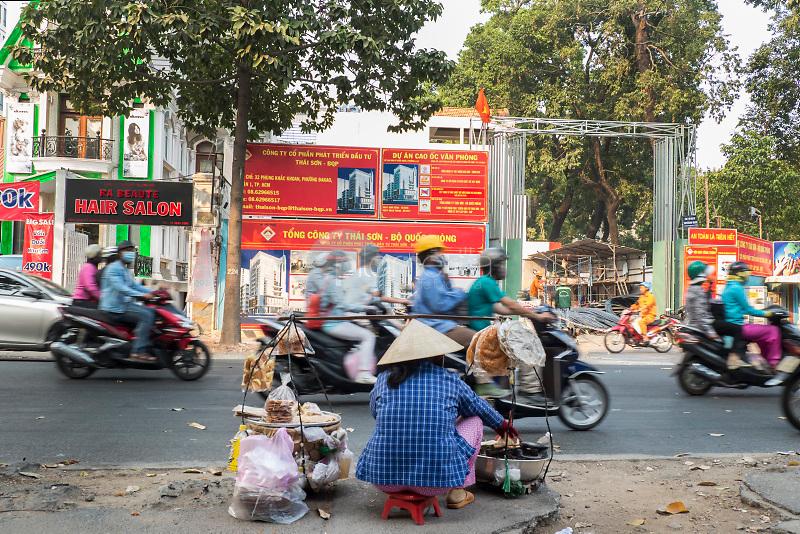 Una mujer vende comida en un puesto callejero de Ho Chi Minh (Saigón). Ataviada con un Nón Lá, el tradicional sombrero cónico vietnamita. ©Iria Pena / PILAR REVILLA