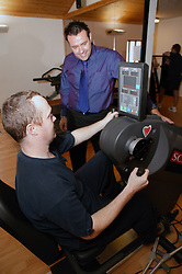 Access to services,  Disabled man in the gym using body building sports equipment,