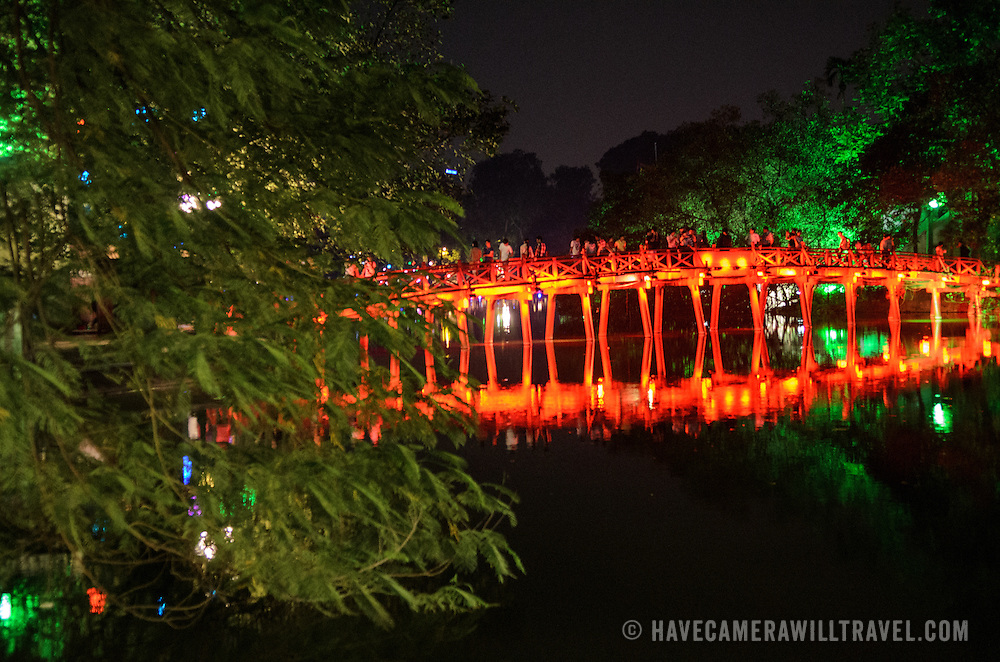 Many tourists visit the The Huc Bridge (Morning Sunlight Bridge) at night. The red-painted, wooden bridge joins the northern shore of the lake with Jade Island and the Temple of the Jade Mountain (Ngoc Son Temple).