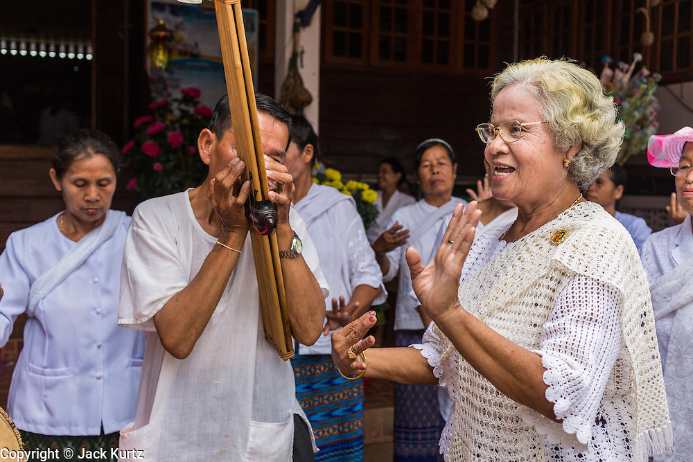 29 JUNE 2014 - DAN SAI, LOEI, THAILAND: A man plays a khaen (a bamboo flute from northern Thailand and Laos) while a woman dances during a merit making procession on the last day of the Ghost Festival in Dan Sai.  Phi Ta Khon (also spelled Pee Ta Khon) is the Ghost Festival. Over three days, the town's residents invite protection from Phra U-pakut, the spirit that lives in the Mun River, which runs through Dan Sai. People in the town and surrounding villages wear costumes made of patchwork and ornate masks and are thought be ghosts who were awoken from the dead when Vessantra Jataka (one of the Buddhas) came out of the forest. On the last day of the festival people participate in merit making ceremonies at the Wat Ponchai in Dan Sai and lead processions through town soliciting donations for the temple.    PHOTO BY JACK KURTZ