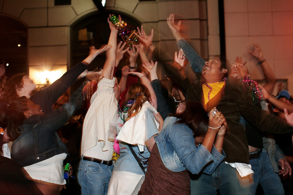 February 28th 2006. New Orleans, Louisiana. United States. .People try to catch beads thrown from a balcony during the celebration of Mardi Gras in the French Quarter.