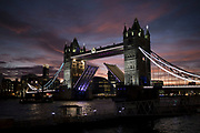 Sunset view of Tower Bridge opening over the River Thames in London, England, United Kingdom. Taken from a riverboat offering a unique view.