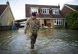 © London News Pictures. 11/02/2014. Wraysbury, UK.  A member of the 1st Battalion of the Royal Regiment of Fusiliers going door to door helping residents in Wraysbury, Surrey, one of the worst hit flood areas in the south east of England. The area has been hit hard by recent flooding from the nearby Thames River. Photo credit : Ben Cawthra/LNP